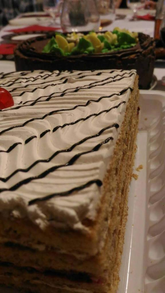 A cake with white icing is seen in the foreground and behind it, a chocolate cake