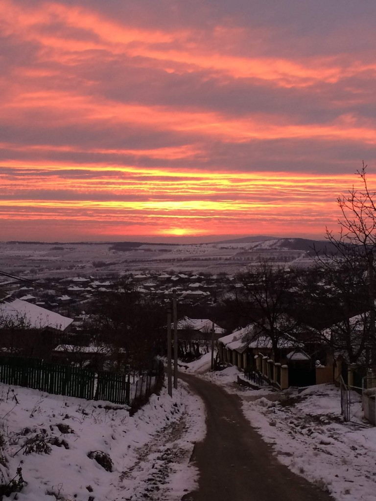 View of some houses with a hill in the background. Snow on the ground is in the foreground. The sky is filled with a beautiful sunset of shades of red and orange.